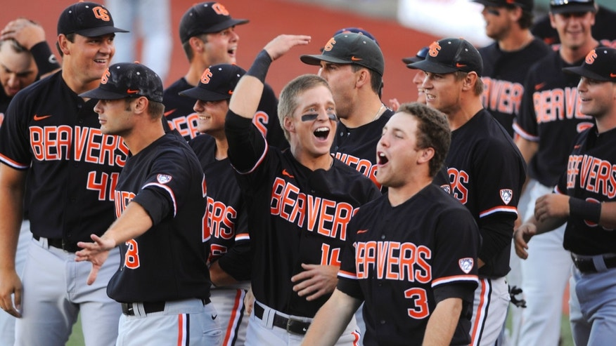 ADVANCE FOR WEEKEND EDITIONS, FEB. 22-23 - FILE - In this June 9, 2013 file photo, Oregon State players celebrate a score by Dylan Davis against Kansas State during the first inning of an NCAA college super regional tournament baseball game in Corvallis, Ore. The traditional powerhouses again pack a lot of punch on the baseball diamond this season. And they each claim to be the toughest in the country. (AP Photo/Greg Wahl-Stephens, File)
