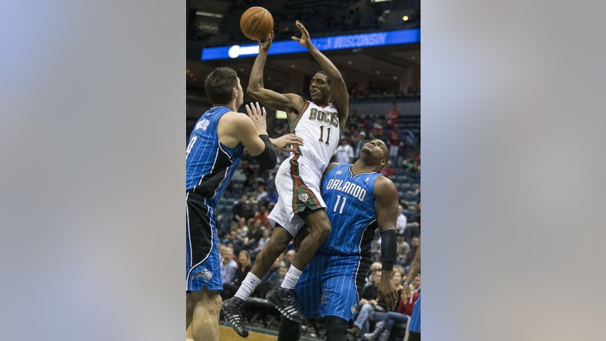 Milwaukee Bucks' Brandon Knight passes the ball off as Orlando Magic's Glen Davis, right, defends during the second half of an NBA basketball game Tuesday, Feb. 18, 2014, in Milwaukee. (AP Photo/Tom Lynn)
