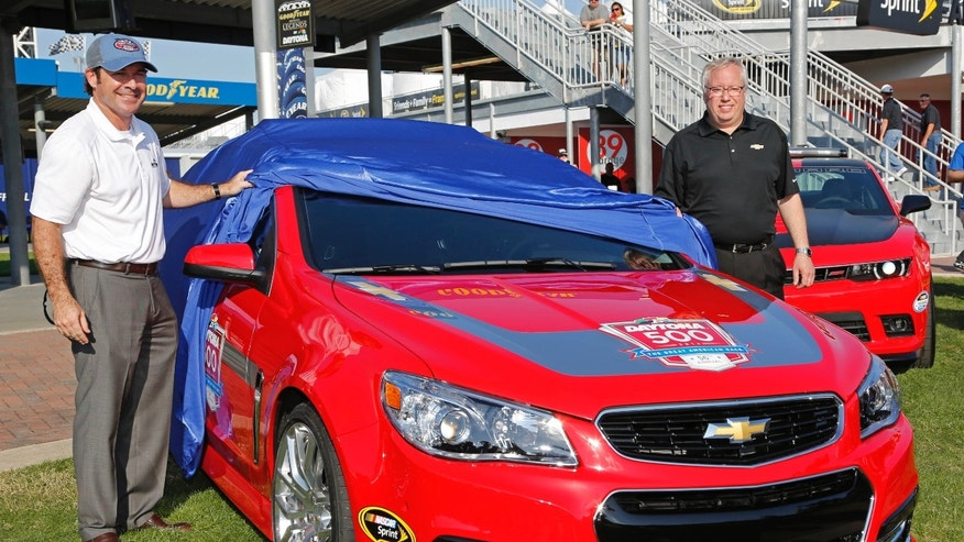Daytona International Speedway president Joie Chitwood, left, and Chevy Racing marketing manager Jeff Chew, right, unveil a new pace car for Sunday's NASCAR Daytona 500 Sprint Cup series auto race in Daytona Beach, Fla., Thursday, Feb. 20, 2014. (AP Photo/Terry Renna)
