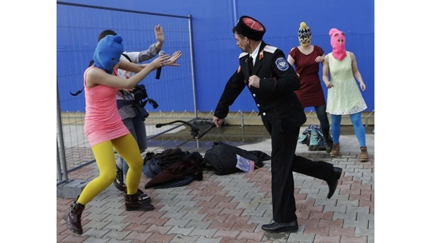 February 19, 2014: A Cossack militiaman attacks Nadezhda Tolokonnikova and a photographer as she and fellow members of the punk group Pussy Riot, including Maria Alekhina, right, in the pink balaclava, stage a protest performance in Sochi, Russia. The group had gathered in a downtown Sochi restaurant, about 21miles from where the Winter Olympics are being held. They ran out of the restaurant wearing brightly colored clothes and ski masks and were set upon by about a dozen Cossacks, who are used by police authorities in Russia to patrol the streets. (AP Photo/Morry Gash)