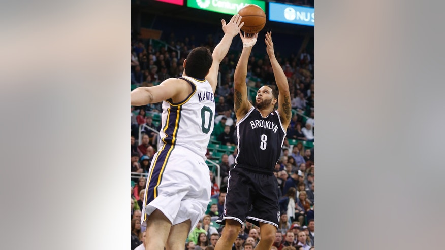 Brooklyn Nets guard Deron Williams (8) takes a shot while defended by Utah Jazz center Enes Kanter (0), of Turkey, during the first half of an NBA basketball game Wednesday, Feb. 19, 2014, in Salt Lake City. (AP Photo/Jim Urquhart)