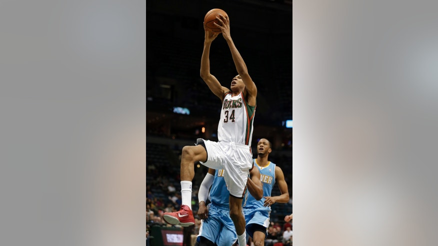 Milwaukee Bucks' Giannis Antetokounmpo (34) dunks against the Denver Nuggets during the second half of an NBA basketball game Thursday, Feb. 20, 2014, in Milwaukee. (AP Photo/Jeffrey Phelps)