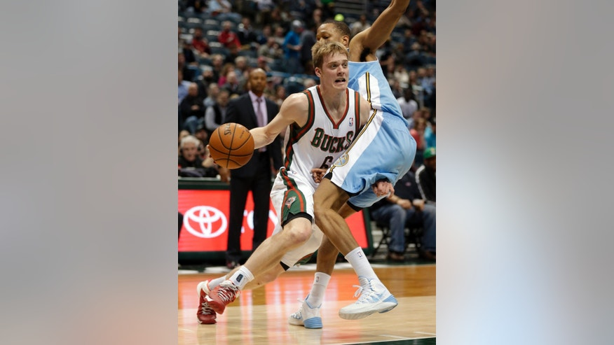 Milwaukee Bucks' Nate Wolters drives against the Denver Nuggets' Anthony Randolph, right, during the second half of an NBA basketball game Thursday, Feb. 20, 2014, in Milwaukee. (AP Photo/Jeffrey Phelps)