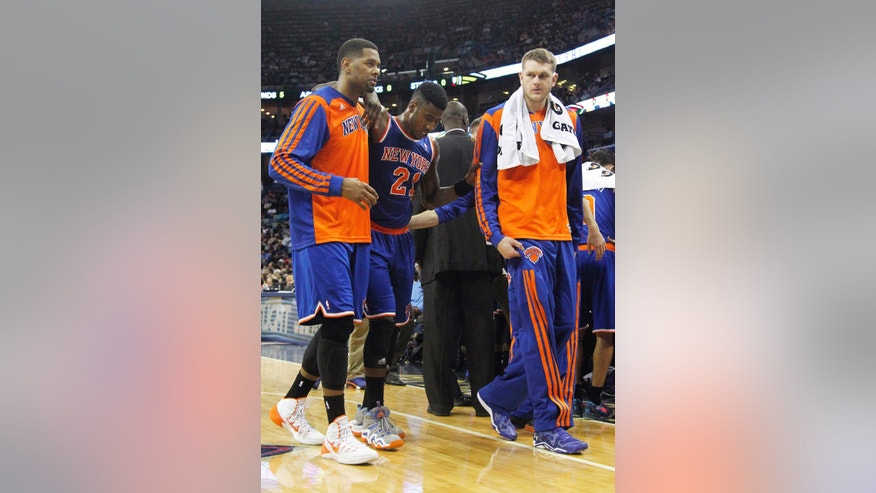 New York Knicks shooting guard Iman Shumpert (21) is helped off the court after being injured during the second half of an NBA basketball game against the New Orleans Pelicans in New Orleans, Wednesday, Feb. 19, 2014. The Knicks won 98-91. (AP Photo/Jonathan Bachman)