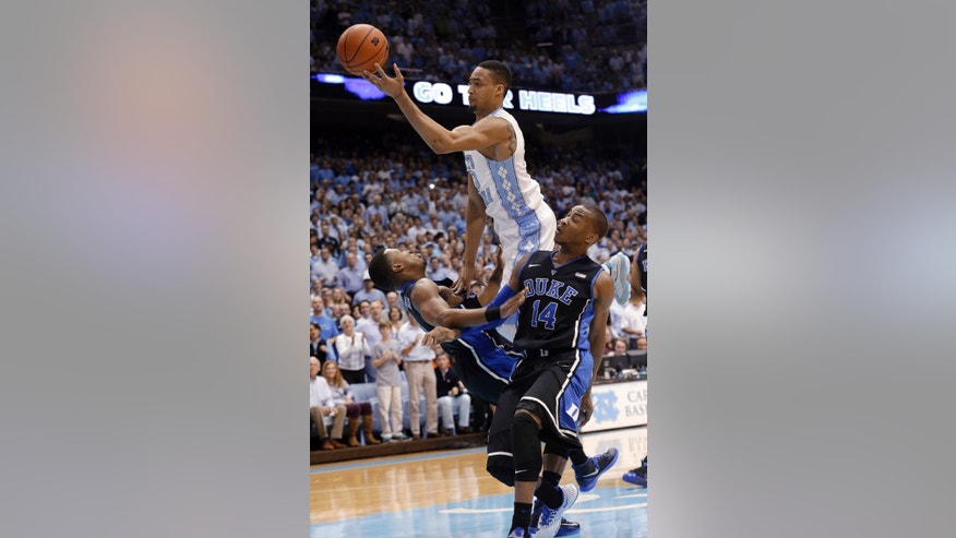 Duke's Tyler Thornton, left and Rasheed Sulaimon (14) defend as North Carolina's J.P. Tokoto drives to the basket during the first half of an NCAA college basketball game in Chapel Hill, N.C., Thursday, Feb. 20, 2014. (AP Photo/Gerry Broome)