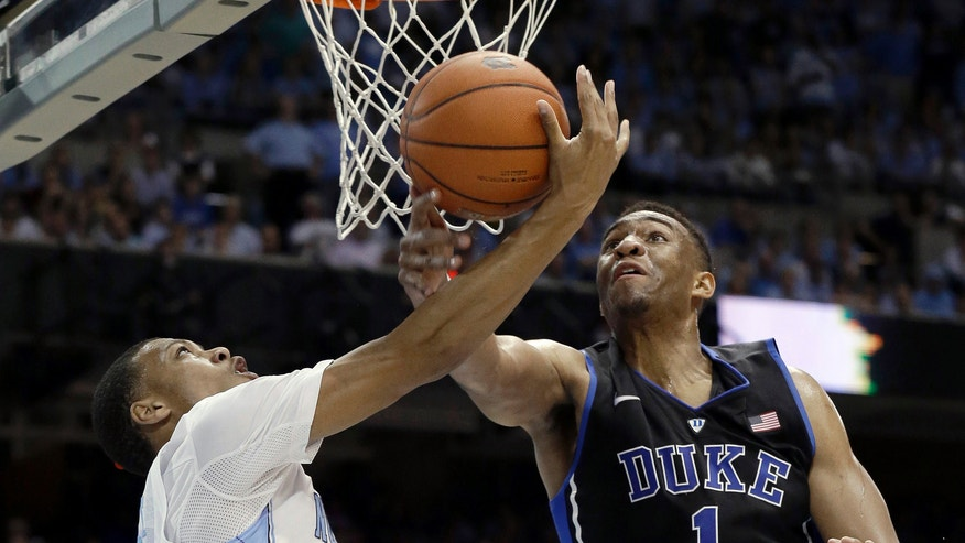 Duke's Jabari Parker (1) blocks North Carolina's Nate Britt during the first half of an NCAA college basketball game in Chapel Hill, N.C., Thursday, Feb. 20, 2014. (AP Photo/Gerry Broome)