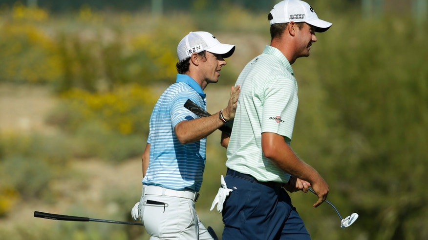 Rory McIlroy, of Northern Ireland, left, pats Harris English on the back English's win during the second round of the Match Play Championship golf tournament Thursday, Feb. 20, 2014, in Marana, Ariz. (AP Photo/Ted S. Warren)