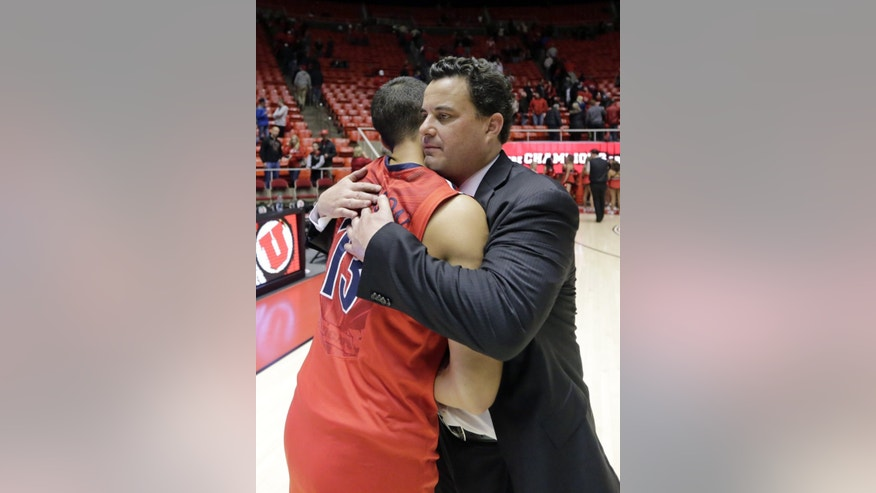 Arizona head coach Sean Miller hugs Nick Johnson (13) at the end of their NCAA college basketball game against Utah Wednesday, Feb. 19, 2014, in Salt Lake City.  Arizona won 67-63. (AP Photo/Rick Bowmer)