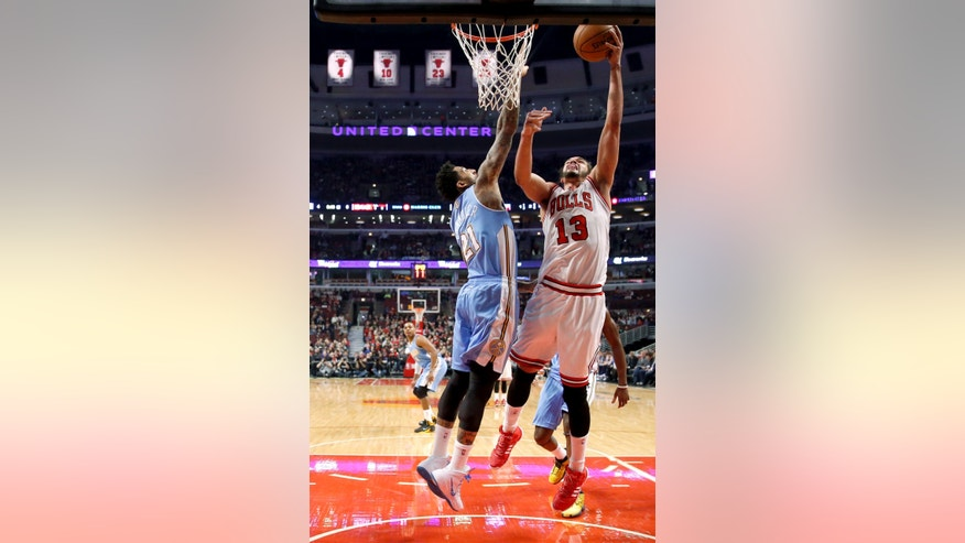 Chicago Bulls center Joakim Noah (13) shoots over Denver Nuggets forward Wilson Chandler (21) during the first half of an NBA basketball game Friday, Feb. 21, 2014, in Chicago. (AP Photo/Charles Rex Arbogast)