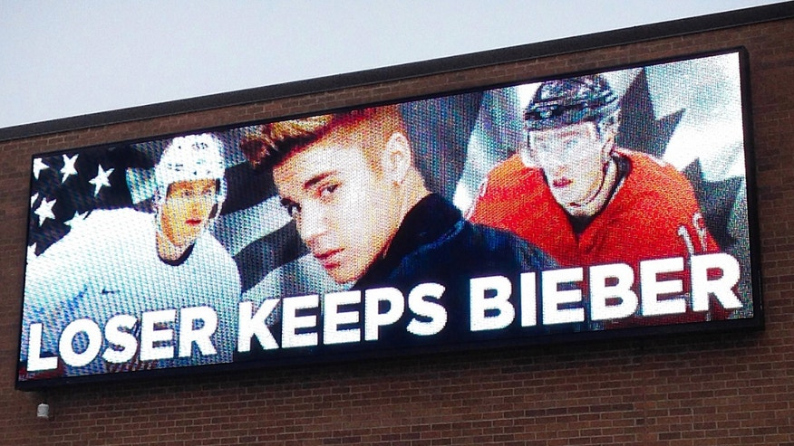 In this photo provided by Command Transportation, an electronic billboard displays pop star Justin Bieber, center, sandwiched by Chicago Blackhawks stars Patrick Kane, left, and Jonathan Toews outside the Skokie, Ill., based freight company. Kane, who plays for Team USA and Toews for Team Canada, played against each other in a men's semifinal ice hockey game at the 2014 Winter Olympics, Friday, Feb. 21, 2014. Canada won 1-0 to advance to the gold medal game. (AP Photo/Command Transportation)