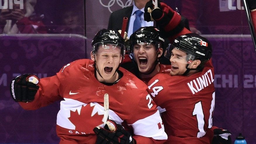 Canada players Corey Perry, left, Matt Duchene, center, and Chris Kunitz, right celebrate on the bench as head coach Mike Babcock looks on after Canada beat the USA 1-0 in a men's semifinal ice hockey game at the 2014 Winter Olympics, Friday, Feb. 21, 2014, in Sochi, Russia. (AP Photo/The Canadian Press, Nathan Denette)