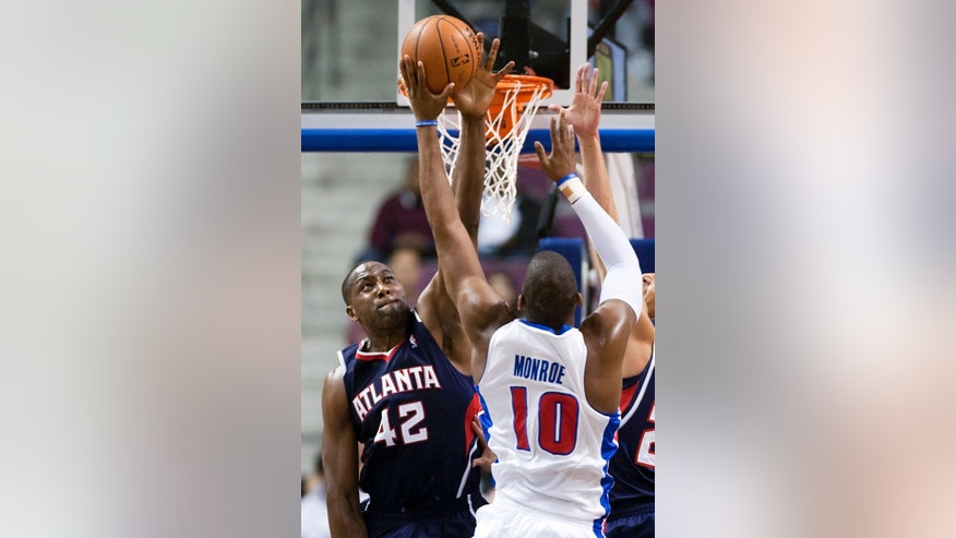 Atlanta Hawks forward Elton Brand (42) blocks a shot by Detroit Pistons center Greg Monroe (10) during the first half of an NBA basketball game, Friday, Feb. 21, 2014, in Auburn Hills, Mich. (AP Photo/Duane Burleson)