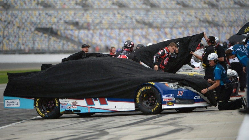 Crew members cover cars as rain falls during qualifying for Saturday's NASCAR Nationwide Series auto race at Daytona International Speedway in Daytona Beach, Fla., Friday, Feb. 21, 2014. (AP Photo/Phelan M. Ebenhack)