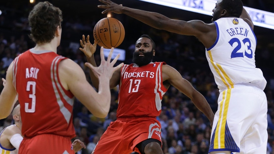 Houston Rockets' James Harden (13) passes away from Golden State Warriors' Draymond Green (23) to Omer Asik (3) during the second half of an NBA basketball game Thursday, Feb. 20, 2014, in Oakland, Calif. (AP Photo/Ben Margot)