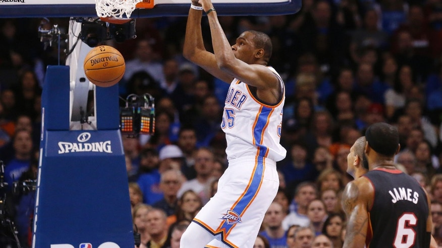 Oklahoma City Thunder forward Kevin Durant dunks in front of Miami Heat forward LeBron James (6) during the first quarter of an NBA basketball game in Oklahoma City, Thursday, Feb. 20, 2014. (AP Photo/Sue Ogrocki)