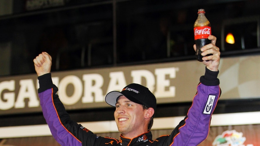 Denny Hamlin celebrates in Victory Lane after winning the second of two NASCAR Sprint Cup series qualifying auto races at Daytona International Speedway in Daytona Beach, Fla., Thursday, Feb. 20, 2014. (AP Photo/Terry Renna)
