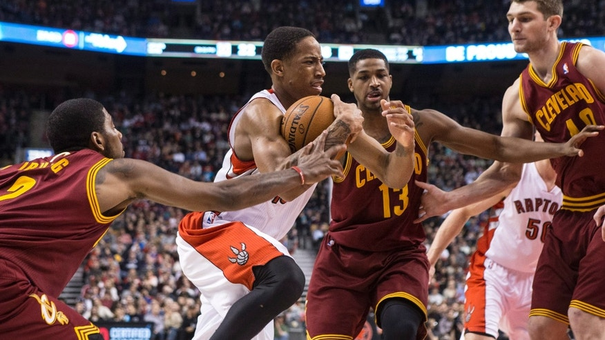 Toronto Raptors' DeMar DeRozan, second from left, drives past Cleveland Cavaliers' Kyrie Irving, left, Tristan Thompson, second from right, and Tyler Zeller to score during first half of an NBA basketball game in Toronto, Friday, Feb. 21, 2014. (AP Photo/The Canadian Press, Chris Young)