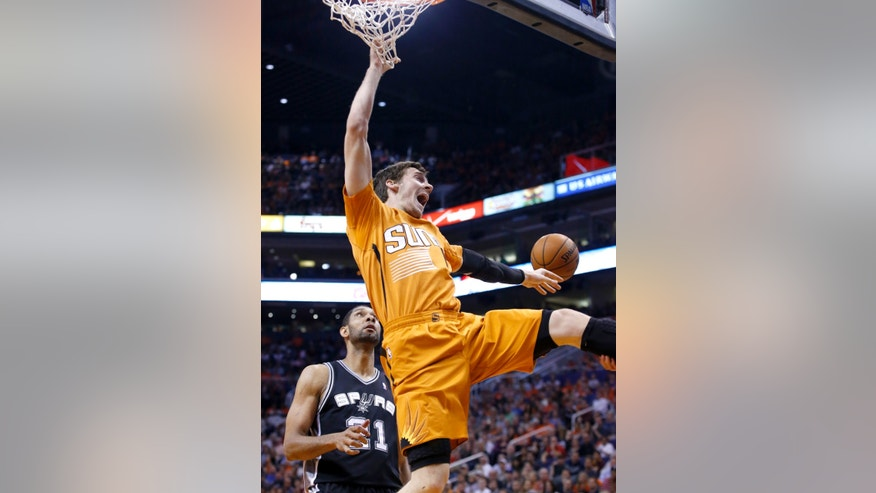 Phoenix Suns' Goran Dragic, right, of Slovenia, loses the ball as San Antonio Spurs' Tim Duncan, left, watches during the first half of an NBA basketball game, Friday, Feb. 21, 2014, in Phoenix. Dragic was called for an offensive foul on the play. (AP Photo/Ross D. Franklin)