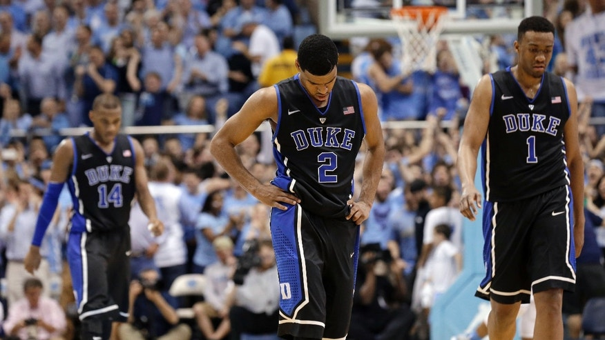 Duke's Rasheed Sulaimon (14), Quinn Cook (2) and Jabari Parker (1) walk off the court during the closing moments of an NCAA college basketball game against North Carolina in Chapel Hill, N.C., Thursday, Feb. 20, 2014. North Carolina won 74-66. (AP Photo/Gerry Broome)