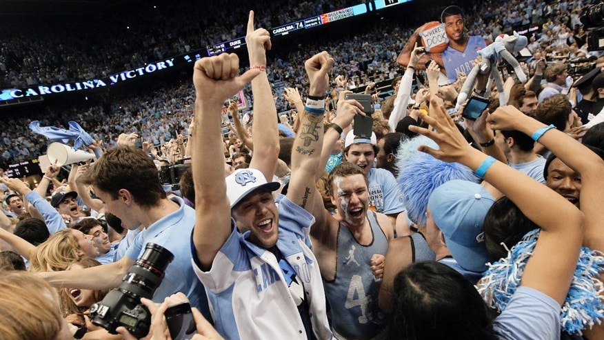 Fans rush the playing court following North Carolina's 74-66 win over Duke in an NCAA college basketball game in Chapel Hill, N.C., Thursday, Feb. 20, 2014. (AP Photo/Gerry Broome)