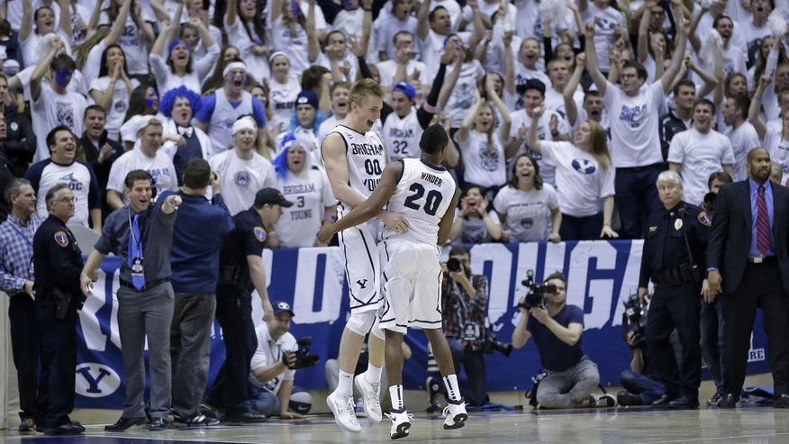 Brigham Young's Eric Mika (00) and teammate Anson Winder (20) celebrate at the end of their NCAA college basketball game against Gonzaga Thursday, Feb. 20, 2014, in Provo, Utah. BYU won 73-65. (AP Photo/Rick Bowmer)