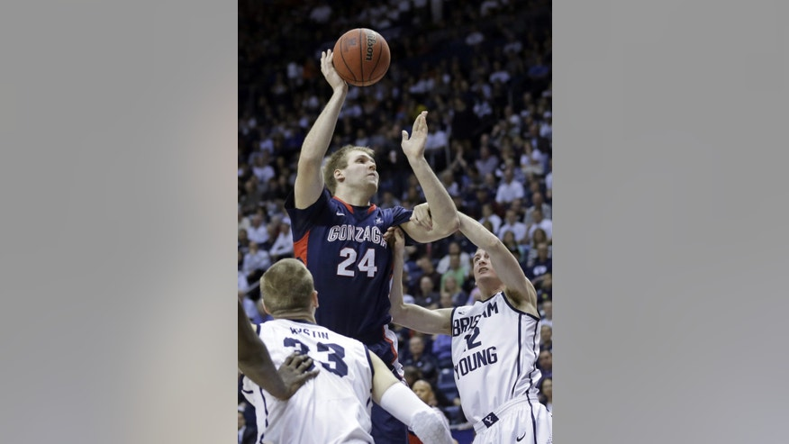 Gonzaga's Przemek Karnowski (24) shoots as Brigham Young's Josh Sharp (12) defends in the first half of an NCAA college basketball game Thursday, Feb. 20, 2014, in Provo, Utah. (AP Photo/Rick Bowmer)