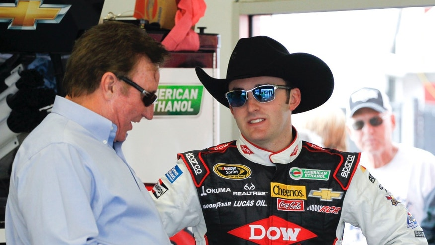 Austin Dillon, right, talks with his grandfather and car owner, Richard Childress, left, in his garage before a practice session for the Daytona 500 NASCAR Sprint Cup Series auto race at Daytona International Speedway in Daytona Beach, Fla., Friday, Feb. 21, 2014. (AP Photo/Terry Renna)