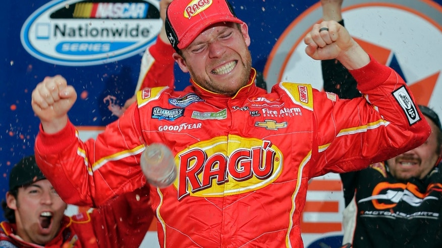 Regan Smith celebrates in Victory Lane after winning the NASCAR Nationwide series auto race at Daytona International Speedway in Daytona Beach, Fla., Saturday, Feb. 22, 2014. (AP Photo/Chuck Burton)