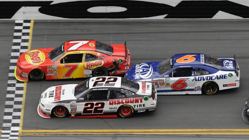 Regan Smith (7) crosses the finish line ahead of Brad Keselowski (22) and Trevor Bayne (6) to win the NASCAR Nationwide Series auto race at Daytona International Speedway in Daytona Beach, Fla., Saturday, Feb. 22, 2014. (AP Photo/John Raoux)