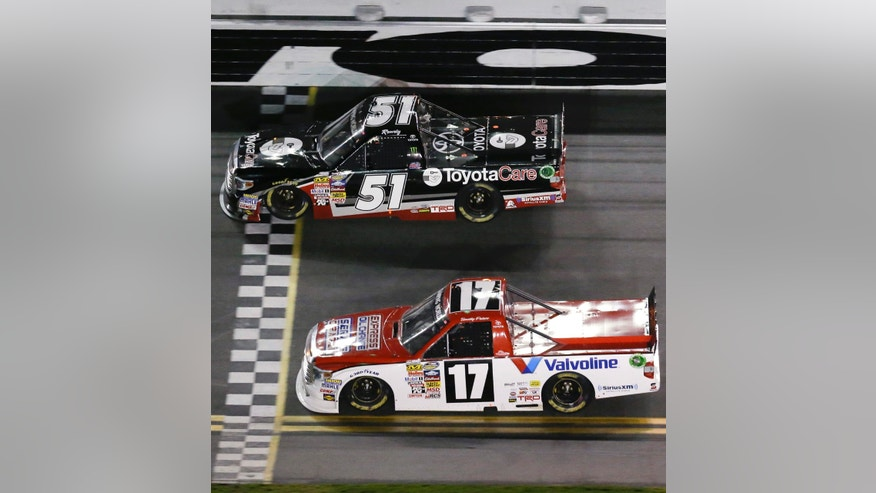 Kyle Busch (51) beats Timothy Peters (17) to the finish line to win the NASCAR Truck Series auto race at Daytona International Speedway in Daytona Beach, Fla., Friday, Feb. 21, 2014. (AP Photo/John Raoux)