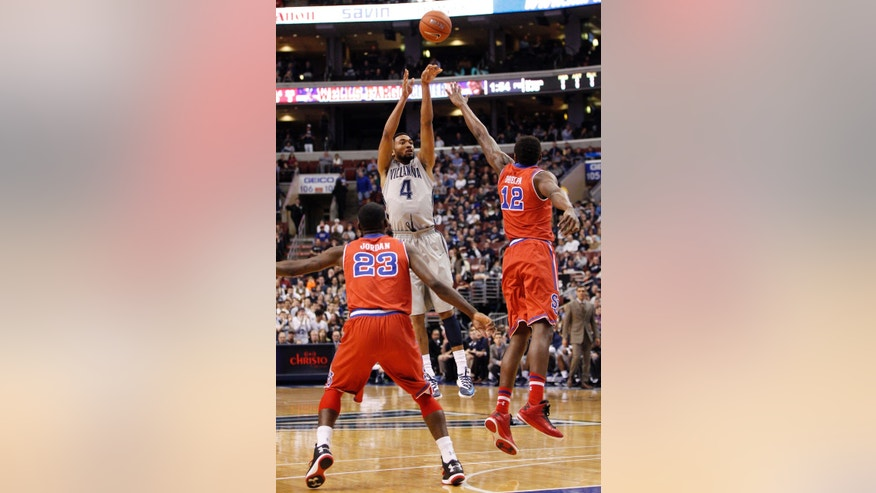 Villanova's Darrun Hilliard II, center, take a three-point shot with St. John's Chris Obekpa, right, of Nigeria, and Rysheed Jordan, left, defending during the first half of an NCAA college basketball game, Saturday, Feb. 22, 2014, in Philadelphia. (AP Photo/Chris Szagola)