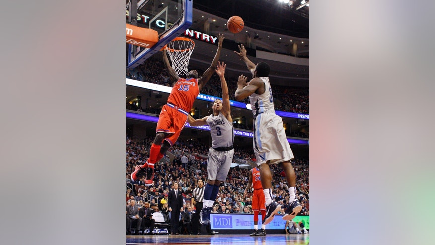 St. John's Sir'Dominic Pointer, left, reaches for the ball while hanging on the basket as Villanova's Josh Hart, center, and Dylan Ennis, right, of Canada, go after it during the first half of an NCAA college basketball game, Saturday, Feb. 22, 2014, in Philadelphia. (AP Photo/Chris Szagola)