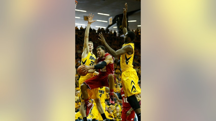 Wisconsin guard Traevon Jackson splits the defense of Iowa forward Jarrod Uthoff and Iowa center Gabriel Olaseni during the first half of an NCAA college basketball game in Iowa City, Iowa, Saturday, Feb. 22, 2014. (AP Photo/Justin Hayworth)