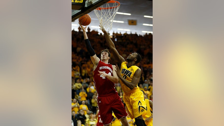 Wisconsin forward Frank Kaminsky puts up a shot past Iowa center Gabriel Olaseni during the first half of an NCAA college basketball game in Iowa City, Iowa, Saturday, Feb. 22, 2014. (AP Photo/Justin Hayworth)