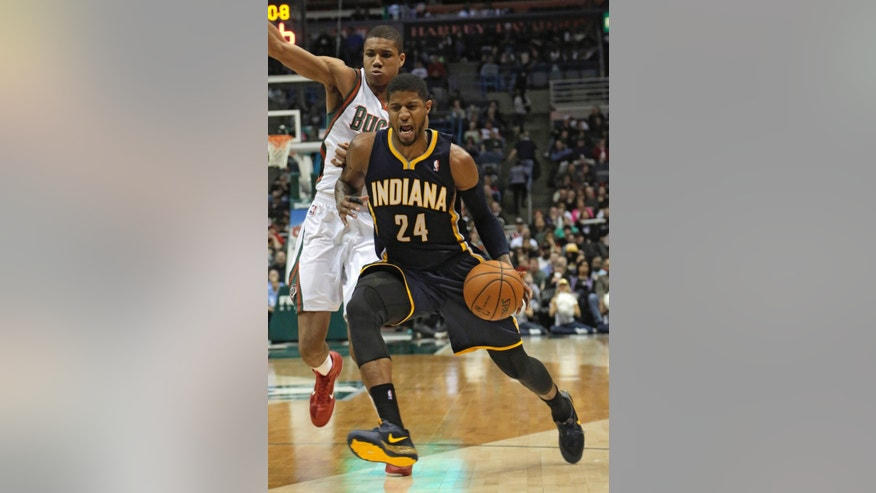 Indiana Pacers forward Paul George (24) drives to the basket against the defense of Milwaukee Bucks guard Giannis Antetokounmpo during the second half of an NBA basketball game Saturday, Feb. 22, 2014, in Milwaukee. (AP Photo/Darren Hauck)