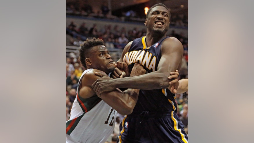 Milwaukee Bucks' Jeff Adrien, left, battles with Indiana Pacers center Roy Hibbert during the second half of an NBA basketball game Saturday, Feb. 22, 2014, in Milwaukee. The Pacers beat the Bucks 110-100. (AP Photo/Darren Hauck)