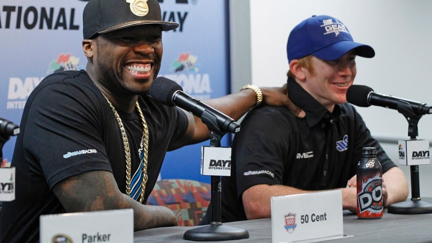 Rapper 50 Cent, left, jokes with driver Cole Whitt, right, during a new conference before practice for Sunday's NASCAR Daytona 500 Sprint Cup series auto race at Daytona International Speedway in Daytona Beach, Fla., Saturday, Feb. 22, 2014. (AP Photo/Terry Renna)
