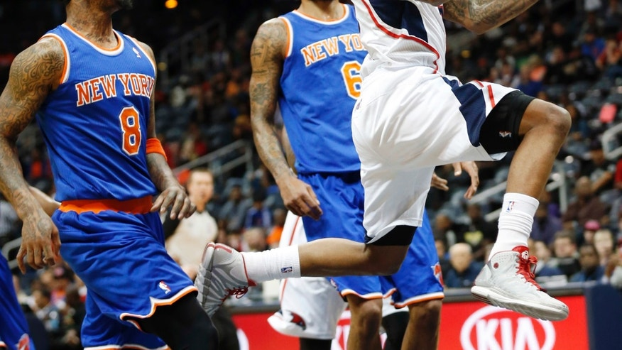 Atlanta Hawks point guard Jeff Teague, right, drives past New York Knicks shooting guard J.R. Smith (8) and center Tyson Chandler (6) to score in the first half of an NBA basketball game Saturday, Feb. 22, 2014, in Atlanta. (AP Photo/John Bazemore)