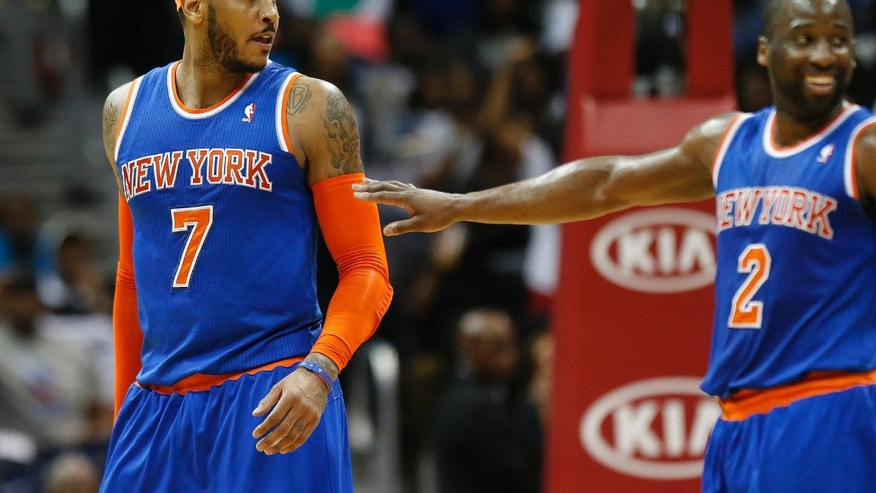 New York Knicks forward Carmelo Anthony (7) is pushed away by teammate Raymond Felton (2) after exchanging word with an Atlanta Hawks player in the second half of an NBA basketball game, Saturday, Feb. 22, 2014, in Atlanta. Atlanta won 107-98.  (AP Photo/John Bazemore)