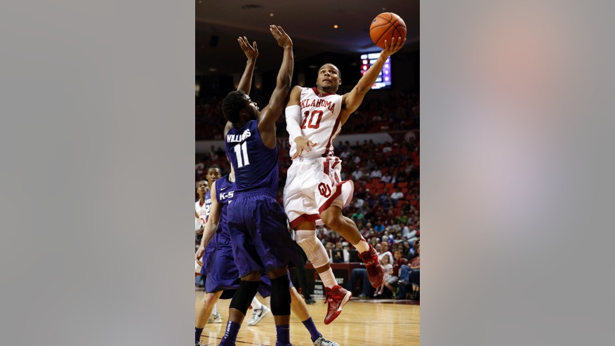 Oklahoma's Jordan Woodard (10) shoots past Kansas State's Nino Williams (11) during the first half of an NCAA college basketball game Saturday, Feb. 22, 2014, in Norman, Okla.  (AP Photo/The Oklahoman, Steve Sisney)
