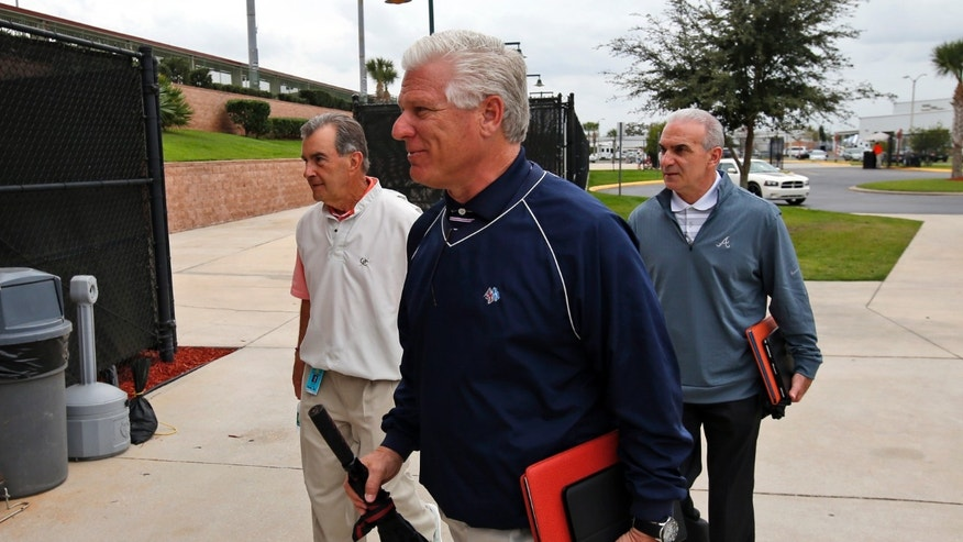 Frank Wren, center, general manager for the Atlanta Braves, and others arrive for a meeting about the new instant replay rules, at the spring training facility for the Astros, Friday, Feb. 21, 2014, in Kissimmee, Fla. (AP Photo/Alex Brandon)
