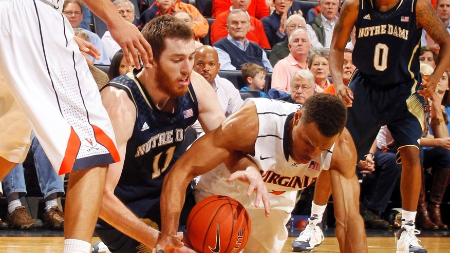 Notre Dame center Garrick Sherman (11) goes after a loose ball with Virginia guard Justin Anderson during an NCAA college basketball game Saturday, Feb. 22, 2014, in Charlottesville, Va. (AP Photo/Andrew Shurtleff)