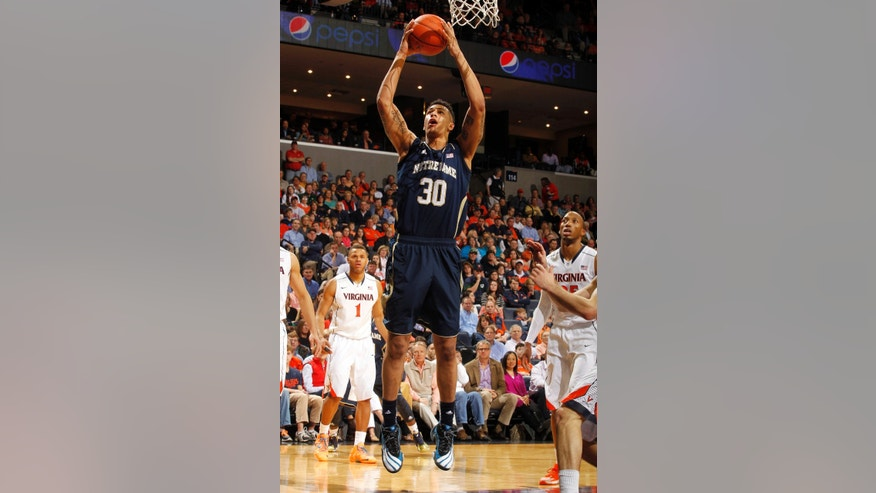 Notre Dame forward Zach Auguste (30) shoots between Virginia defenders during an NCAA college basketball game Saturday, Feb. 22, 2014, in Charlottesville, Va. (AP Photo/Andrew Shurtleff)