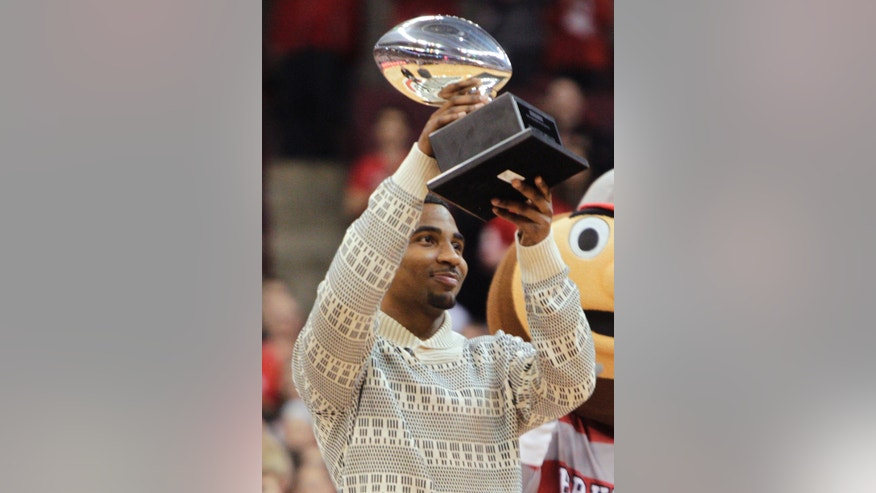 Ohio State quarterback Braxton Miller raises the Silver Football, awarded by the Chicago Tribune to the best football player in the Big 10, during a timeout in an NCAA college basketball game between Ohio State and Northwestern on Wednesday, Feb. 19, 2014, in Columbus, Ohio. (AP Photo/Jay LaPrete)