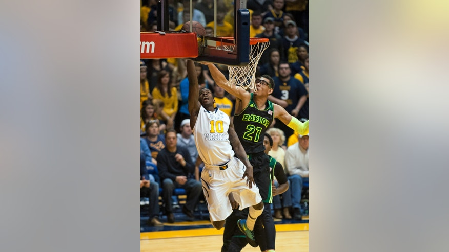 West Virginia's Eron Harris, left, lays in a basket as Baylor's Isaiah Austin defends during the first half of an NCAA college basketball game Saturday, Feb. 22, 2014, in Morgantown, W.Va. (AP Photo/Andrew Ferguson)