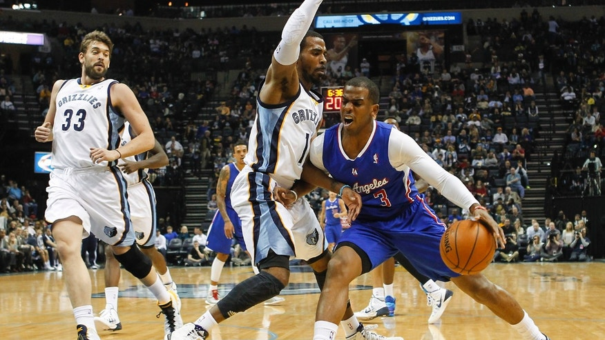 Los Angeles Clippers guard Chris Paul (3) goes to the basket against Memphis Grizzlies guard Mike Conley (11) and center Marc Gasol (33), of Spain, in the first half of an NBA basketball game Friday, Feb. 21, 2014, in Memphis, Tenn. (AP Photo/Lance Murphey)