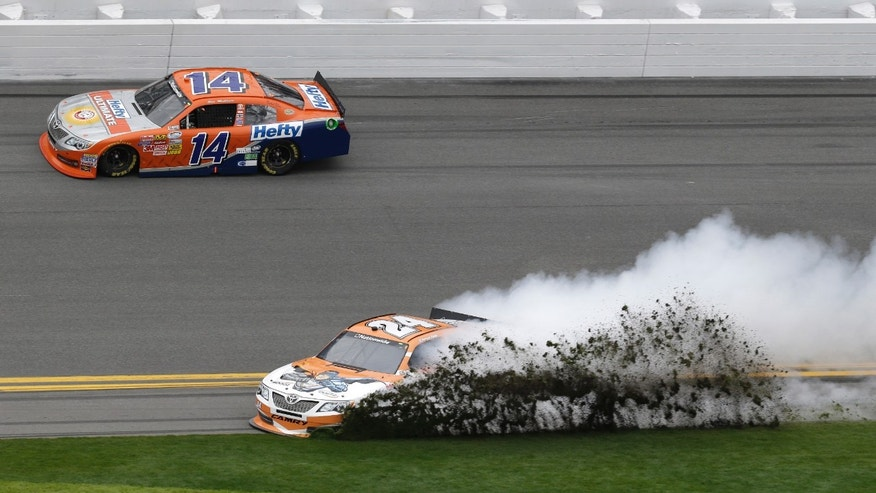 Grass flies as Harrison Rhodes (24) spins during the NASCAR Nationwide series auto race at Daytona International Speedway in Daytona Beach, Fla., Saturday, Feb. 22, 2014. Eric McClure (14) drives past at top. (AP Photo/John Raoux)