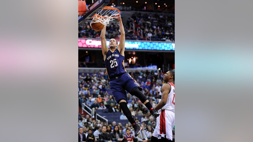 New Orleans Pelicans guard Austin Rivers (25) dunks against Washington Wizards center Kevin Seraphin, right, of France, during the first half of an NBA basketball game, Saturday, Feb. 22, 2014, in Washington. (AP Photo/Nick Wass)