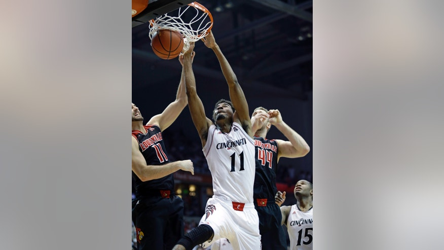 Cincinnati forward Jermaine Lawrence (11) dunks against Louisville guard Luke Hancock, left, and forward Stephan Van Treese (44) in the first half of an NCAA college basketball game, Saturday, Feb. 22, 2014, in Cincinnati. (AP Photo/Al Behrman)