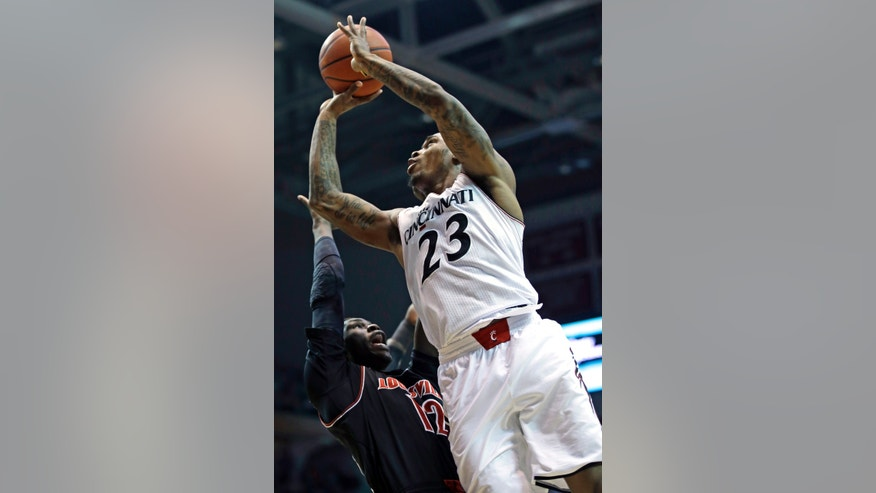 Cincinnati guard Sean Kilpatrick (23) shoots over Louisville forward Mangok Mathiang (12) in the first half of an NCAA college basketball game, Saturday, Feb. 22, 2014, in Cincinnati. (AP Photo/Al Behrman)